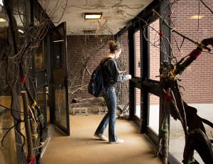 A student exits the College of Architecture and Planning building. Student installations are featured throughout the building.